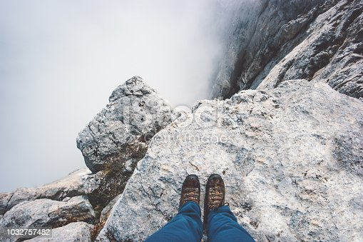 Traveler Feet boots on rocky mountain cliff over foggy clouds Travel Lifestyle success concept adventure active vacations outdoor top view