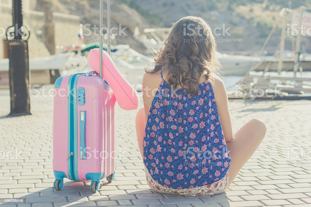 Traveler girl is sitting with pink suitcase royalty-free stock photo