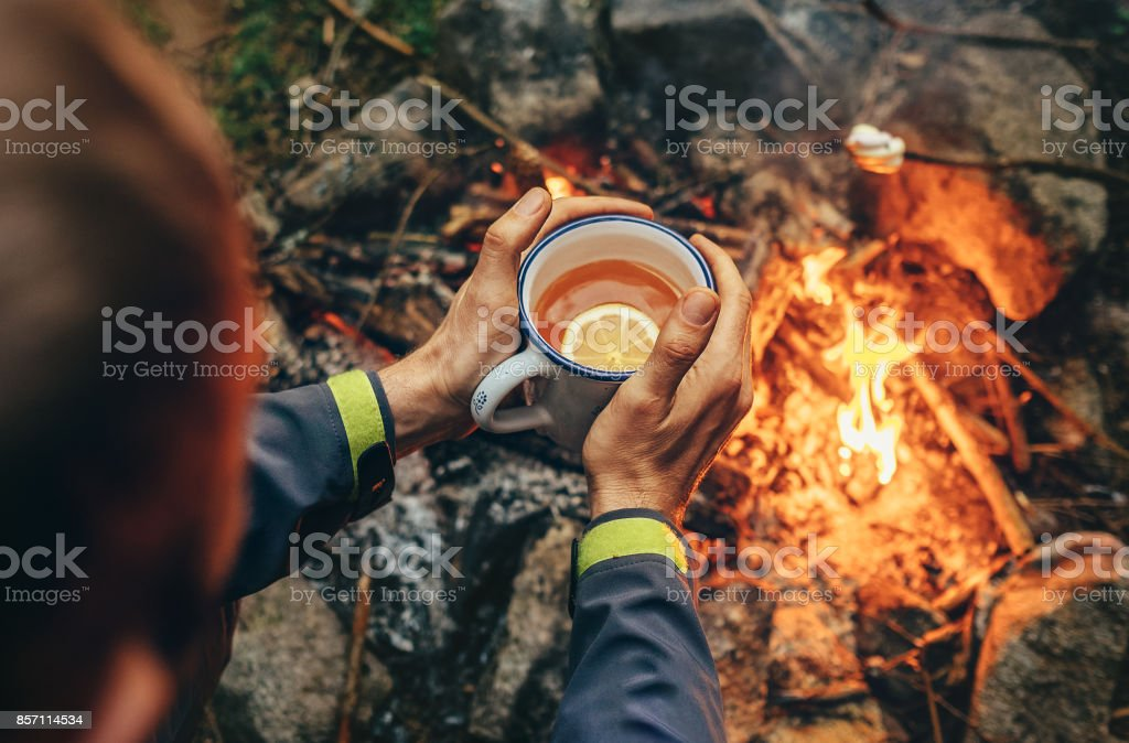Traveler hand with big mug of hot tea near campfire stock photo