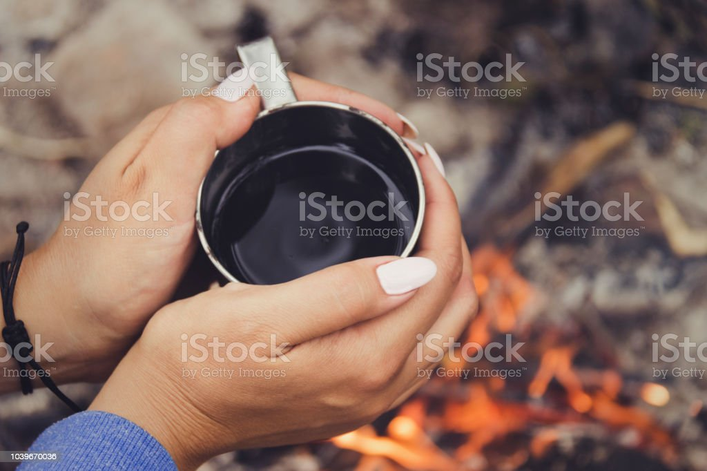 Traveler hands holding mug from thermos near the bonfire. Drinking coffee or tea from mug at camp stock photo