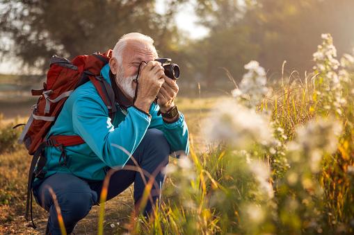 Traveler hiker man with backpack hiking near lake taking photos
