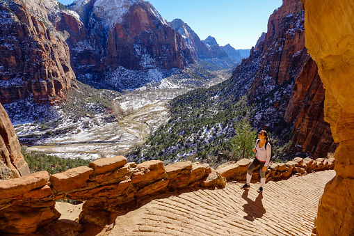 fit female traveler hikes along the angel's landing hiking path on a sunny winter day. woman visiting zion national park observes the spectacular wintry canyon while walking along a scenic trail.
