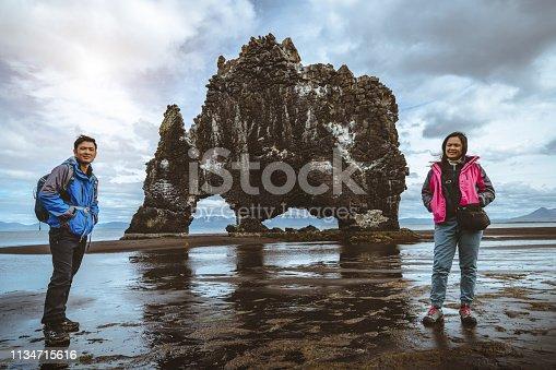 Traveler hiking to Hvitserkur, unique basalt rock landscape in Iceland. The majestic Hvitserkur is a 15 meter high monolith standing offshore of Vatnsnes peninsula in North-West Iceland, Europe.