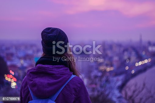 istock Traveler hipster looking at winter evening cityscape and purple sky 610769978