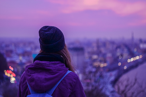 Traveler hipster looking at winter evening cityscape and purple sky