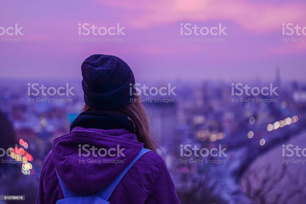 Traveler hipster looking at winter evening cityscape and purple sky - Photo