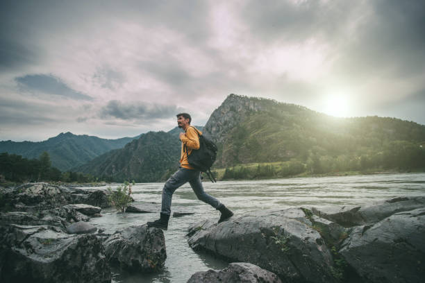 Traveler hipster man walking in front of beautiful mountain landscape. stock photo
