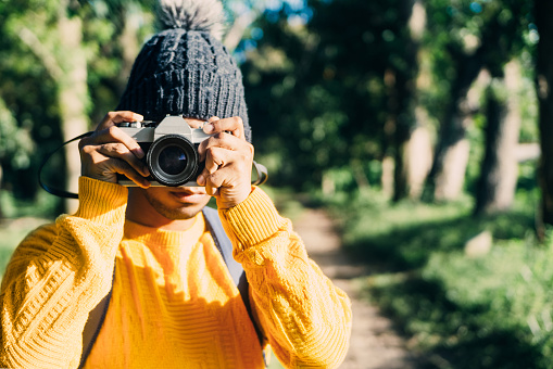 young hispanic traveler holding an analog camera taking a photo. nature travel.