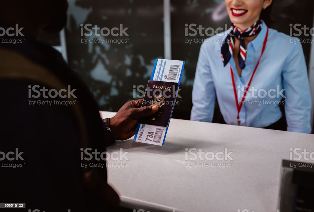 Traveler holding passport and boarding pass at airport check-in counter stock photo