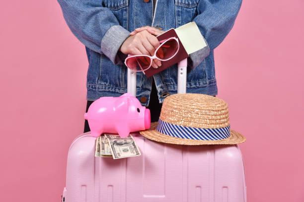 reisenden mit rosa koffer, passagier- und pass dokumentieren über rosa hintergrund, geld geld sparen und reisen konzept. - geld schön verpacken stock-fotos und bilder