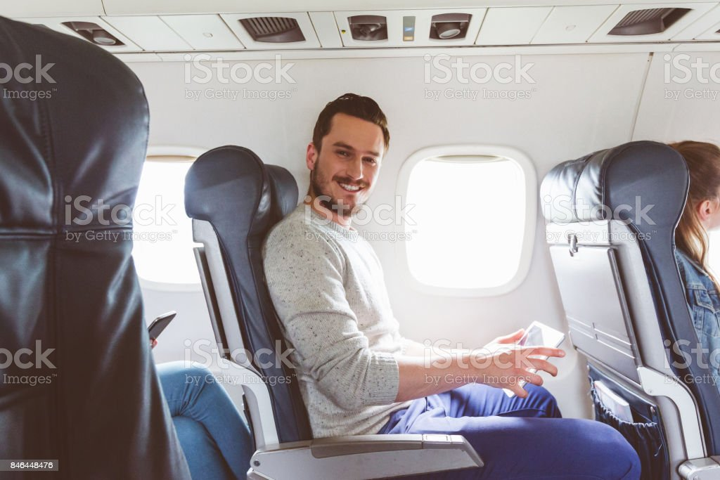 Traveler in flight with tablet computer stock photo