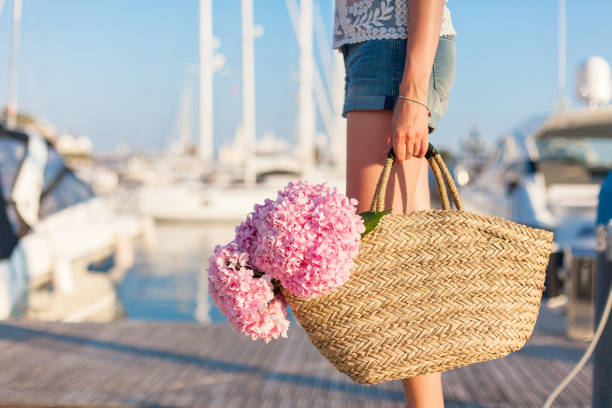 Traveler is standing in yachts port near sea with straw bag and pink flowers hydrangea. Girl has vacation in resort. stock photo