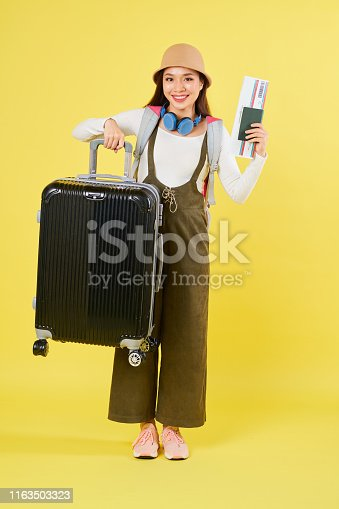 Full-length portrait of cheerful Vietnamese woman showing plane ticket and lifting her big suitcase
