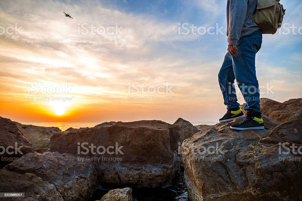 traveler looking at airplane at sunset stock photo