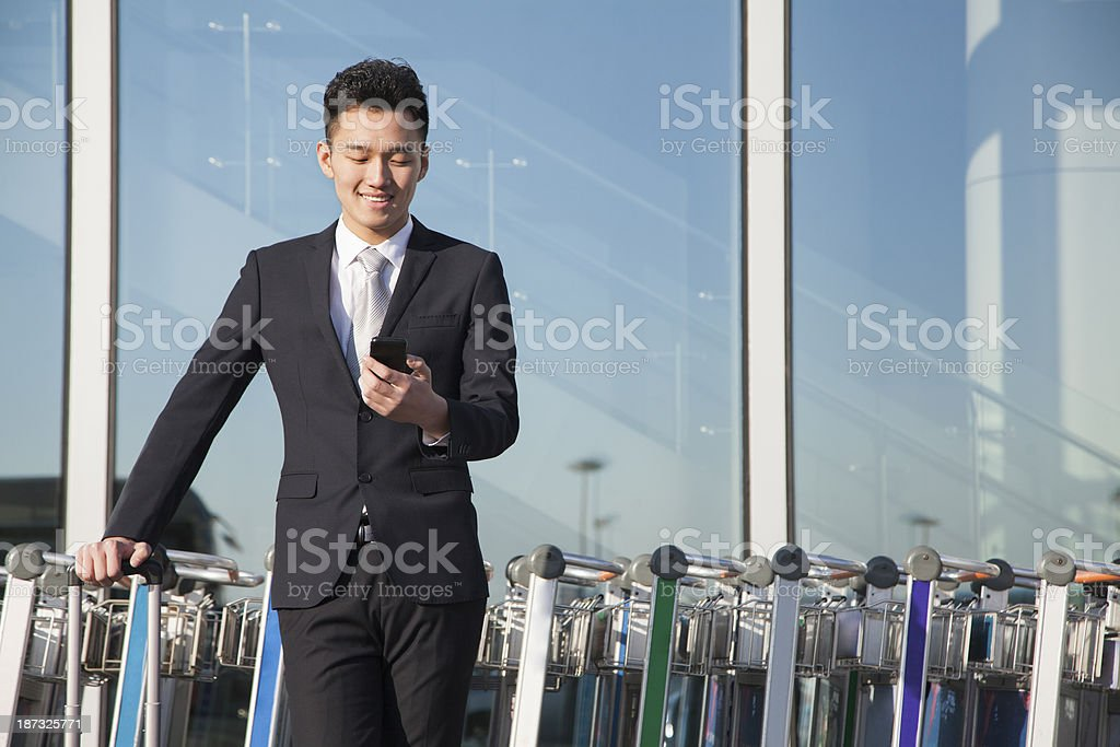 Traveler looking at cellphone next to row of luggage carts stock photo