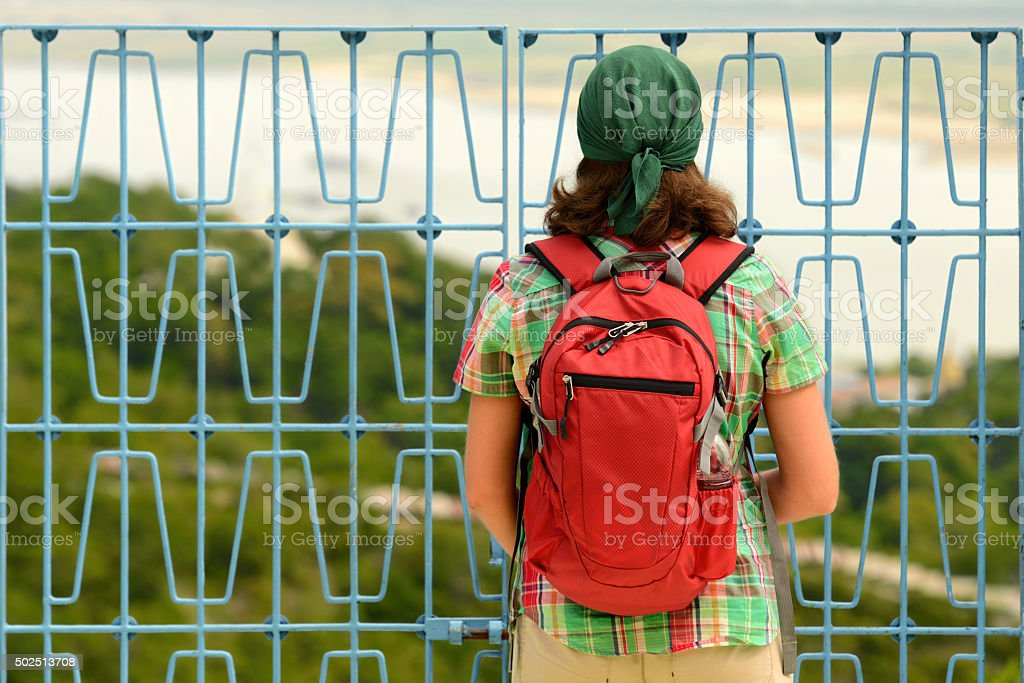 traveler looking through metal fence at closed area to visit. stock photo