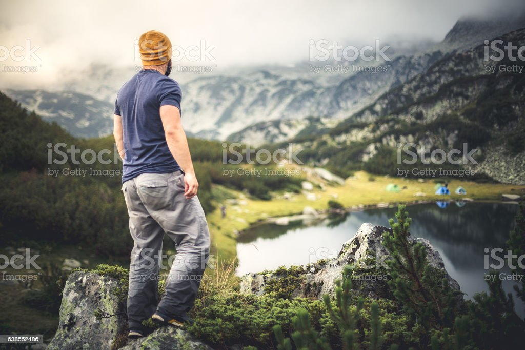 Traveler looks on camping near lake in mountains stock photo