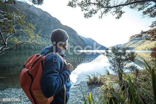 istock Traveler man by the mountain lake contemplates beautiful landscape 625977280