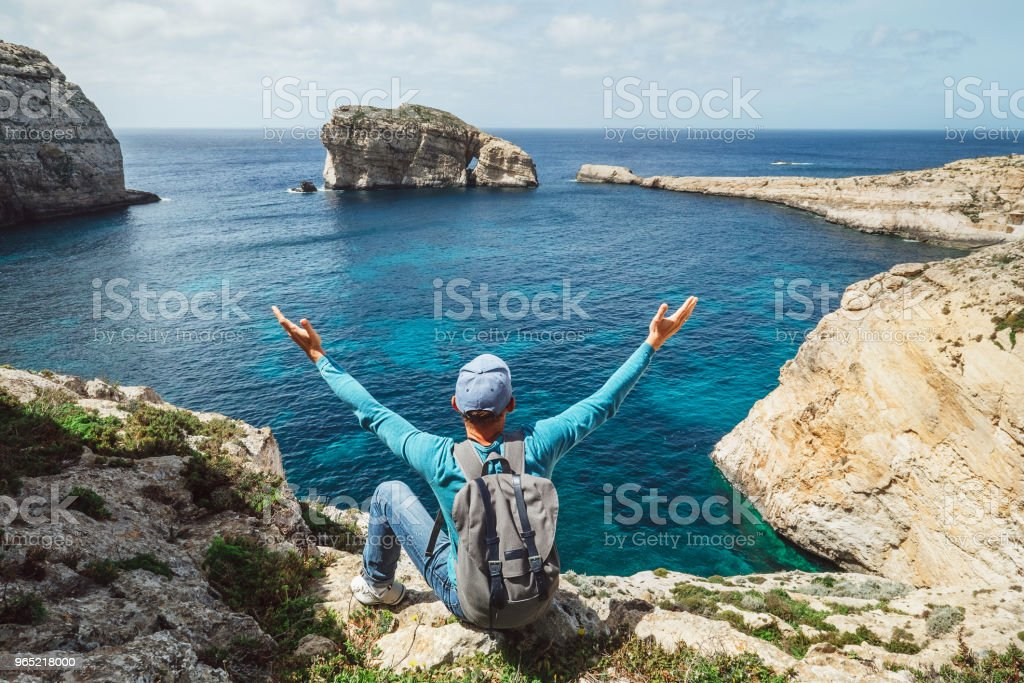 Traveler man feels free seeting on the rocky seaside of blue lagoon royalty-free stock photo