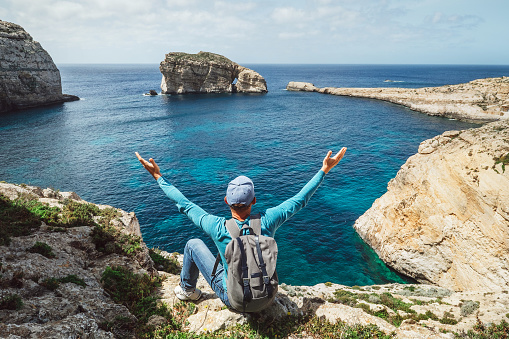 Traveler Man Feels Free Seeting On The Rocky Seaside Of Blue Lagoon Stock Photo - Download Image Now