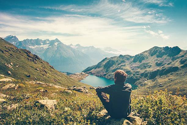 Traveler Man relaxing Travel Lifestyle mountains and lake landscape stock photo