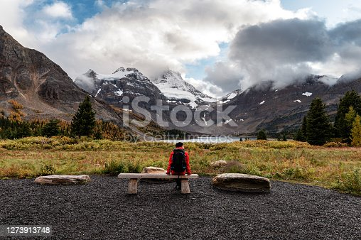istock Traveler man sitting on beach with mount assiniboine and lake magog in provincial park 1273913748