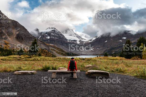 Photo of Traveler man sitting on beach with mount assiniboine and lake magog in provincial park