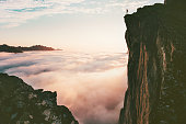 istock Traveler man standing on the edge cliff over clouds sunset mountains travel adventure lifestyle journey vacations in Norway 1263881571