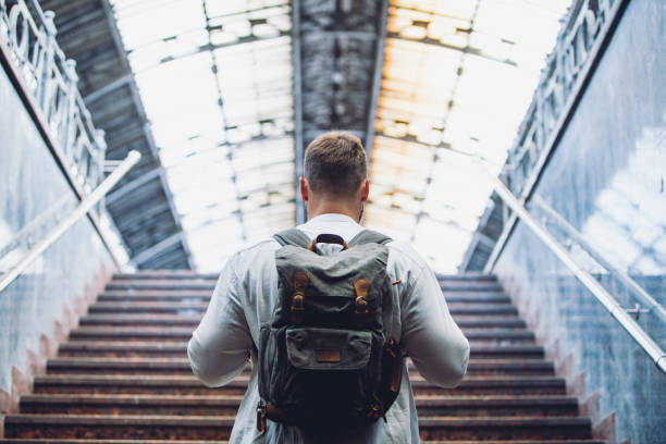 traveler man with backpack walking up by stairs stock photo