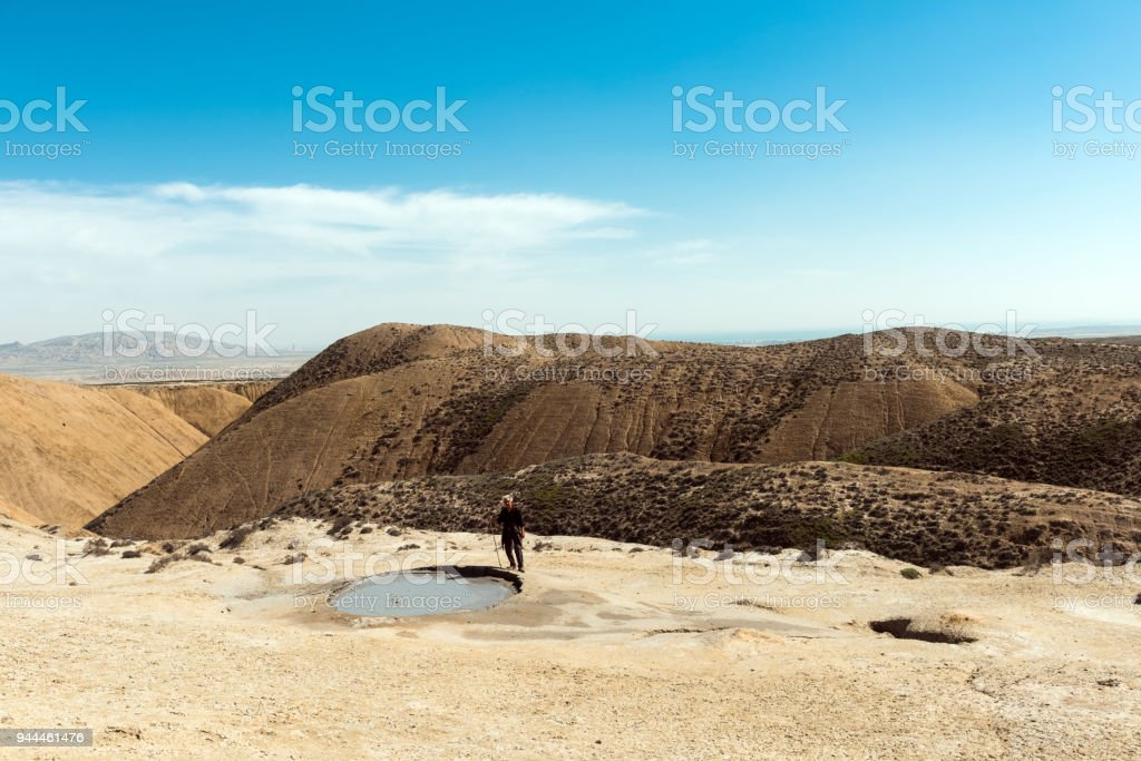 A traveler near the crater of a mud volcano stock photo