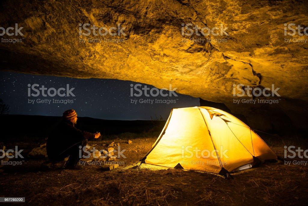 Viajante perto da barraca de acampamento brilhante na gruta à noite sob um céu estrelado - foto de acervo