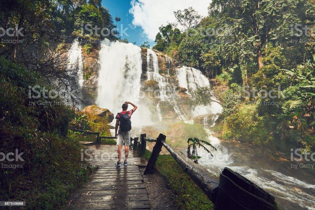 Traveler near waterfall stock photo