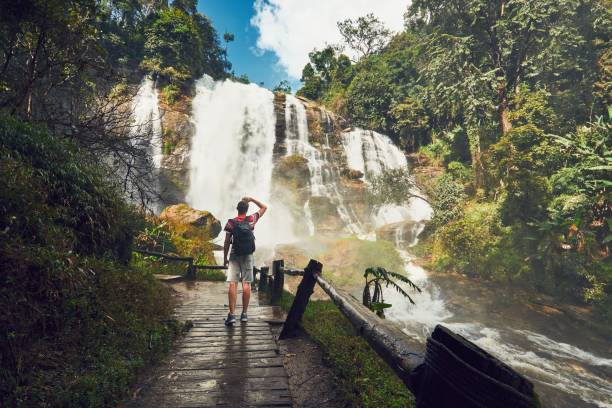 Traveler near waterfall Young man (traveler) standing near Wachirathan waterfall in tropical rainforest. Chiang Mai Province, Thailand chiang mai province stock pictures, royalty-free photos & images