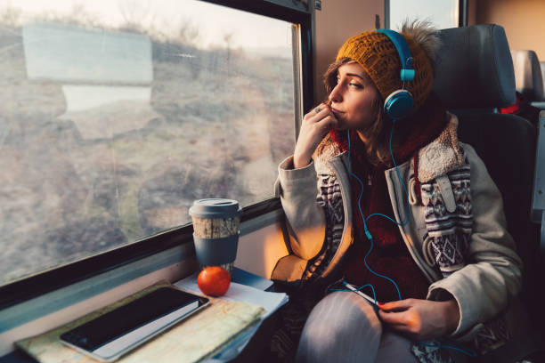 Traveler on a journey with train Thoughtful woman in the train looking through the window mental wellbeing stock pictures, royalty-free photos & images