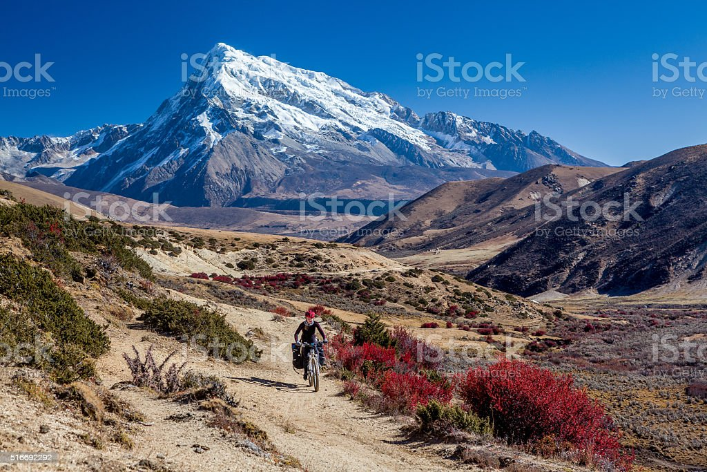 Traveler on mountain bike cycling trail in mountains stock photo