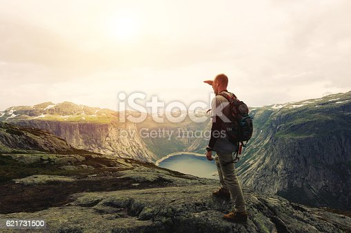 Young brave traveler on the top of a mountain plateau looks into the distance