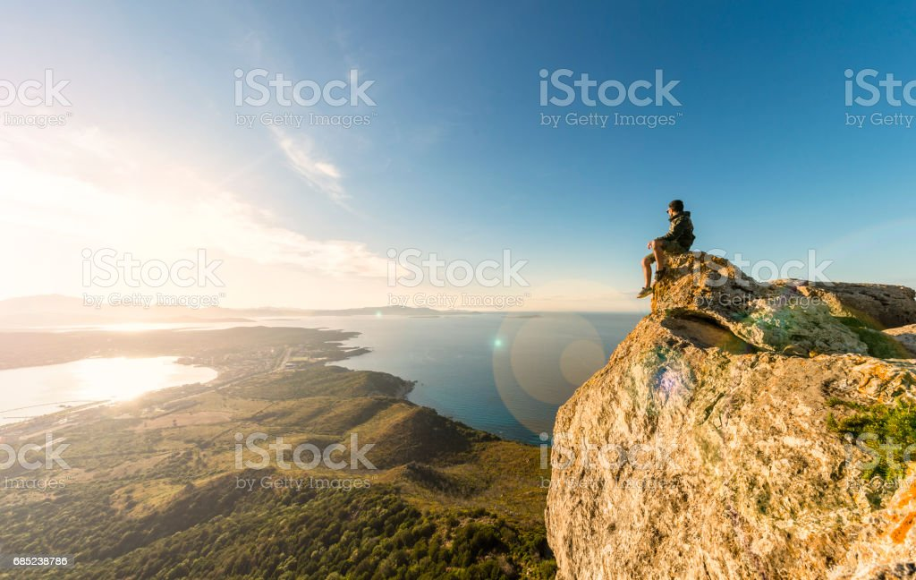 A traveler on the top of the mountain is enjoying the stunning view at sunset in Sardinia, Italy. foto de stock royalty-free