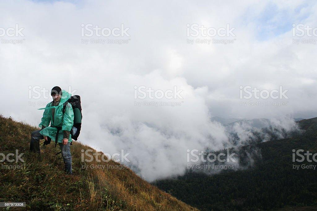 Traveler on top of mountain in sky. stock photo