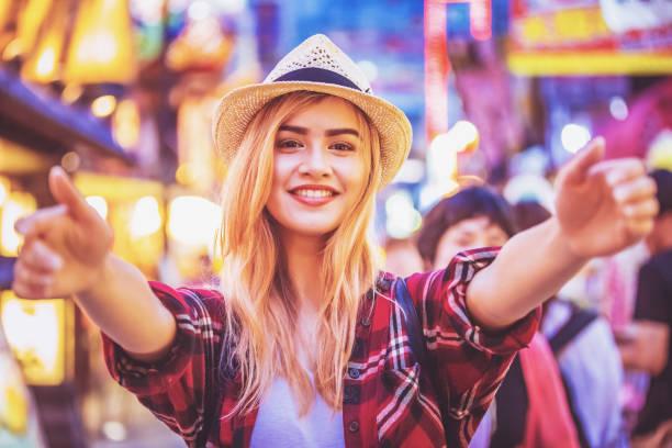 旅行者がカメラに向かって抱擁で彼女の手を開く - 背景に人 ストックフォトと画像