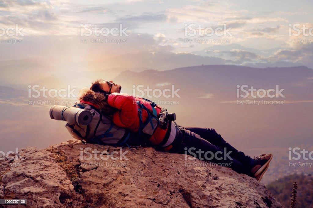 Gezgin veya bir dağın tepesinde oturan uzun yürüyüşe çıkan kimse stok fotoğrafı