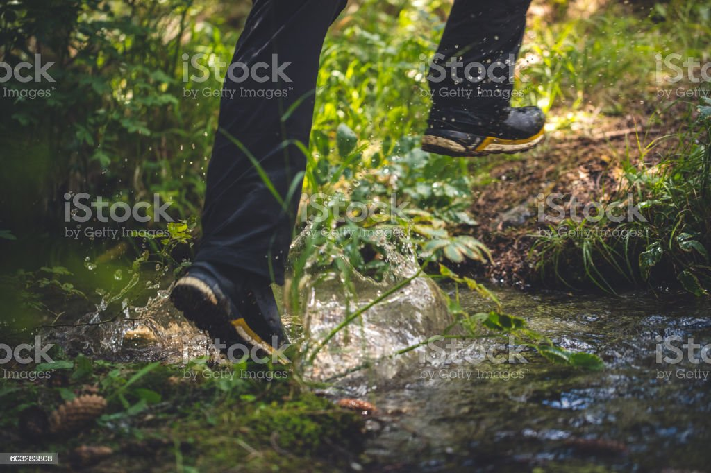 Traveler passes a stream in the woods – Foto