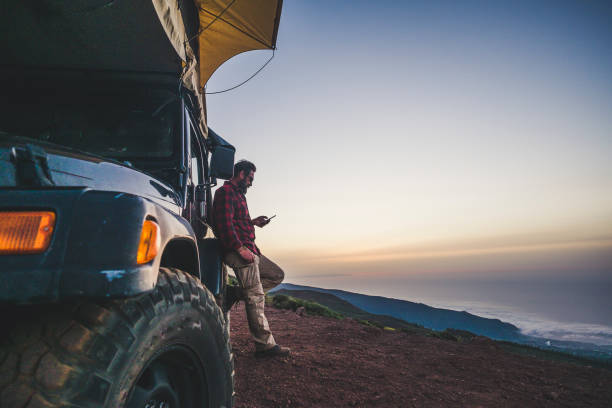 Traveler people with car and camping concept - lonely man use cellular phone to connect to internet outside his vehicle - mountain and nature outdoor around - enjoying freedom and alternative vacation with independence stock photo