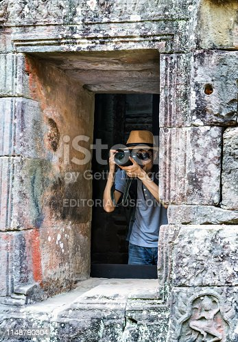 SIEM REAP, CAMBODIA - March 01, 2015: Traveler photographer asian man in hat Angkor Wat is a popular tourist attraction temple in Angkor Cambodia. Ancient Khmer architecture in jungle.