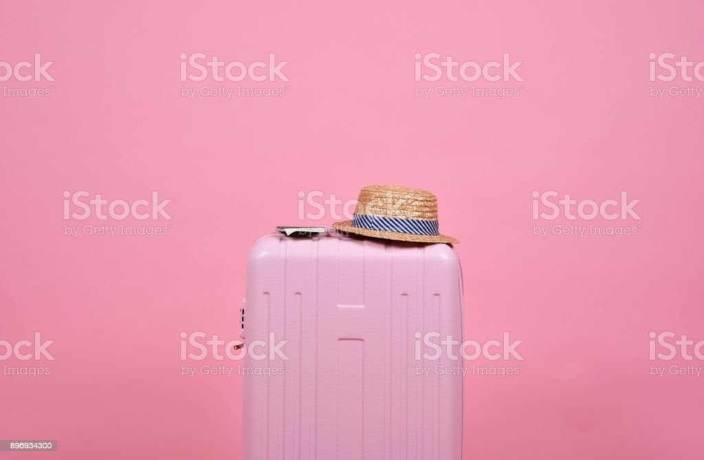 Traveler pink suitcase and passport document over pink background, Journey and travel concept. stock photo