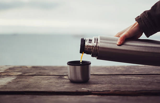 traveler pouring tea from thermos - flask stock photos and pictures