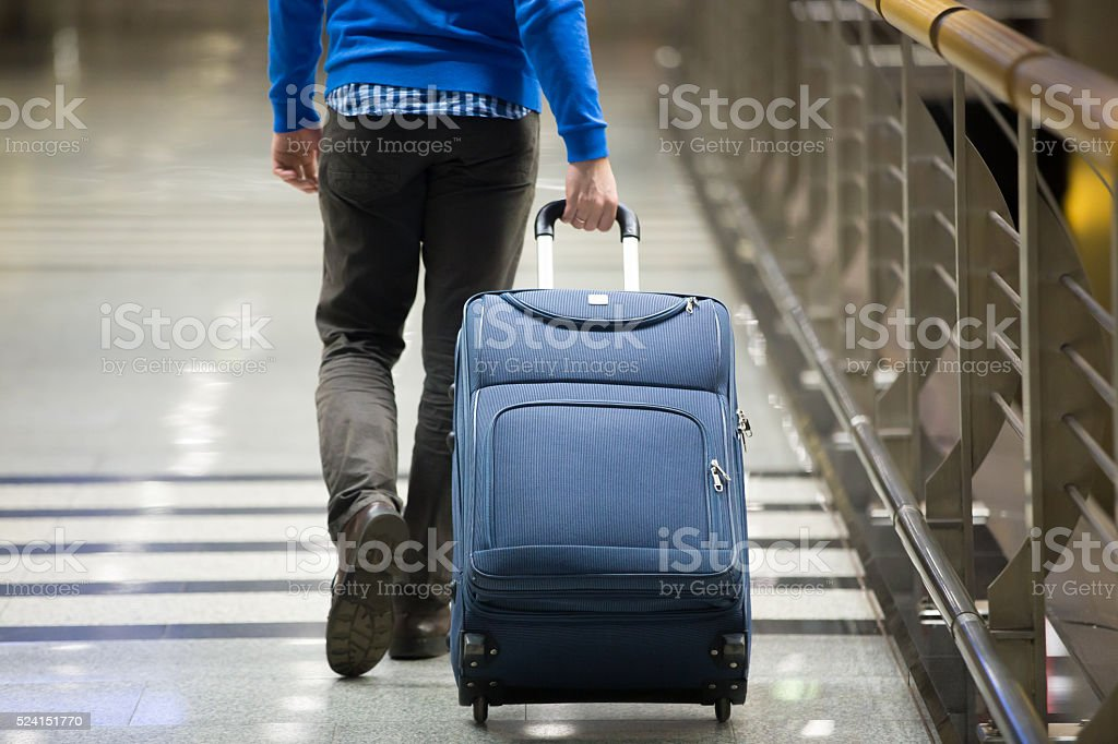 Traveler pulling suitcase close-up stock photo