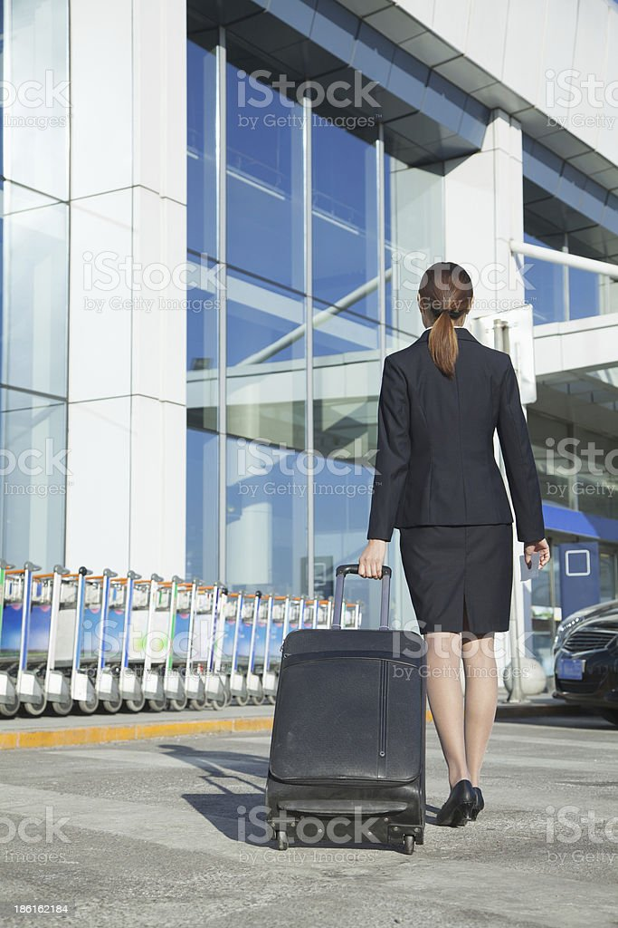 Traveler pulling suitcase into airport royalty-free stock photo