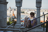 A young woman traveling in Hungary reads her guidebook while sitting at Fisherman's Bastion in Budapest. The Hungarian Parliament is visible below, beside the Danube River. (June 2013)