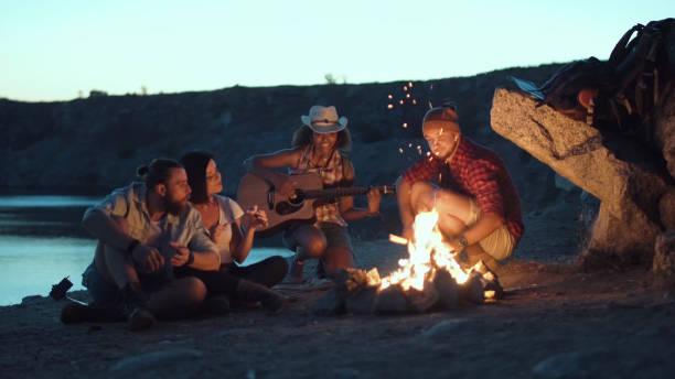 Traveler relaxing at bonfire on shore stock photo