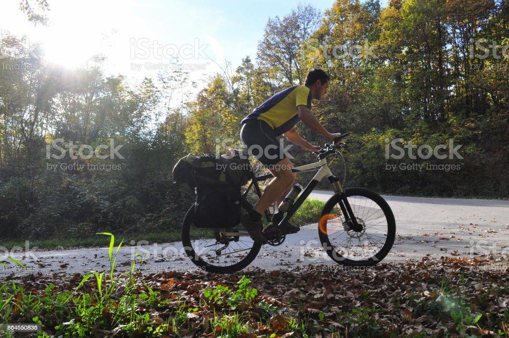 Viajero de paseos en bicicleta por una sinuosa carretera de montaña - foto de stock
